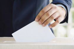 persona echando una papeleta en unas elecciones