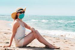 Mujer en la playa con mascarilla y distancia de seguridad