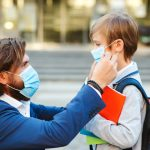 padre y niño con mascarilla saliendo del colegio