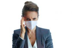 Mujer con dolor de cabeza por llevar mascarilla mucho tiempo