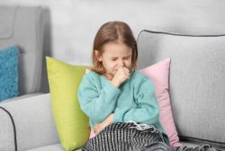 Niña en el sofá con bronquitis